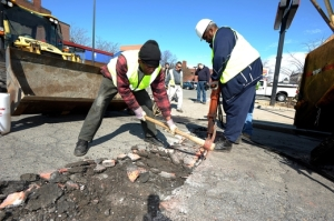 Boston Public Works Department employees Aroll Victor and Julio Echemendia clear rocks from a pothole in South Boston on March 12.