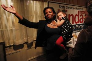 Linda Dorcena Forry held her daughter Madeline Forry, 2, as she celebrated a possible close victory at Phillips Freeport Tavern in Dorchester. (taken before Nick Collins conceded.)