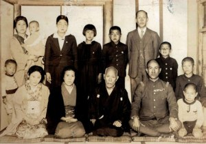 Together with my father who returned briefly from Manchuria in 1939. Front row from left: my mother Yukie, grandmother Tsuki, grandfather Kosaburo, father Chikara, younger brother Sadamu, and myself behind Sadamu, together with my uncle Eijiro Sata's family in back row.